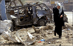 An Iraqi woman walks from the wreckage of a mini-bus at the bus station.