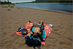 Rick Mellentine, of Mazomanie, Wis., reads on Mazomanie Beach, a nude beach where an increased number of recent drug and sex crimes have forced state wardens to patrol the beachfront more frequently.