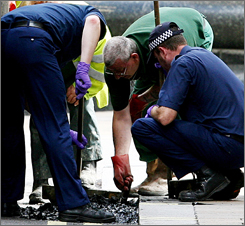 Police officers search a drain near Piccadilly Circus in central London on Friday.