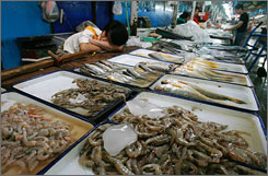 A vendor selling shrimps and fish naps while waiting for customers at a seafood market in Beijing June 29, 2007. China is the largest producer of farmed fish, handling 50% of the total value of global aquacultured seafood exports around the world.