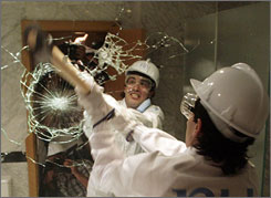 A man smashes a mirror in a Madrid hotel, Tuesday. Spanish hotel chain NH organized the promotional event which involved the smashing up of one floor of the hotel before its remodelling.