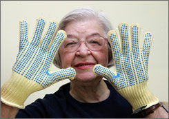 Stephanie Kwolek models household gloves that incorporate Kevlar, which she had a big hand in inventing while working as one of the few female scientists at Dupont in the mid-1960s.