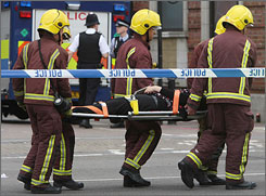 An injured passenger is carried by fire brigade officers after evacuation from Mile End station on July 5, 2007 in London. Up to six carraiges of a London Underground train came off the rails during the morning rush hour.