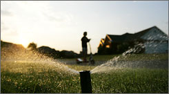 Sprinklers water a homeowners yard in Montgomery, Ala. Police in Alabama and other states are being called on to enforce mandatory and voluntary bans on water use as a drought grips the Southeast.