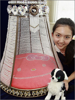 Japan maker Sanrio's employee, Fumina Takada, displays a doghouse, designed with a Hello Kitty and decorated with 7,600 Swarovski crystals.