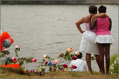 Longtime friends of Michelle McIntosh, Karen Nelson, left, embraces her daughter, Georgette Nelson, near a memorial set up at the edge of a pond at Beardsley Park in Bridgeport, Conn on Thursday. McIntosh chased after her minivan and tried to climb in just as it rolled into the park pond Wednesday with her son, nephew and another child inside. All four died.