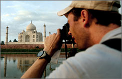 A tourist takes pictures of the 17th century Mughal-built Taj Mahal mausoleum, in Agra, Saturday. The Taj Mahal is one of the 10 frontrunners out of 21 short-listed sites in competition to become one of the 'new' seven wonders of the world.
