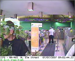 This security camera photo provided by the police shows a bank robber, left, wearing a disguise of leaves duct taped to his head and torso in the Citizens Bank, in Manchester, N.H. Saturday, July 7, 2007.