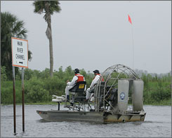 A pair of men in an airboat take a ride down the Kissimmee River, Fla. The river hasn't flowed south in more than 240 days, depriving Lake Okeechobee, the heart of the Everglades, of 50% of its water.