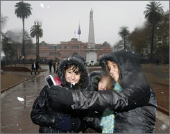 Argentinian girls take a picture with a mobile phone in front of the presidential palace July 9, 2007, while the first snow in 89 years falls. Temperatures hit -8 degrees Fahrenheit, breaking a 30-year record.