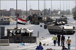 U.S military forces use their armoured vehicles to block a road after their convoy was hit by a roadside bomb attack in Baghdad July 3.