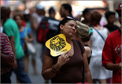 A woman uses a hand fan to cool herself in New York City. The city is experiencing some of the hottest weather of the summer so far with temperatures in the upper 90's.