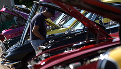 Car fans stroll past a line of muscle cars and classics at the Villa Restaurant Car Show in a Detroit suburb.