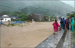 Residents watch a road flood with mud waters in Minami-Osumi town in Kagoshima Prefecture, southwestern Japan, Saturday, as Typhoon Man-Yi cut power and snarled transportation.