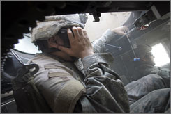 A U.S. soldier slouches from the gunner's turret of his Humvee holding his head after an improvised explosive device hit the vehicle in March during a patrol in a predominantly Sunni neighborhood of southern Baghdad.