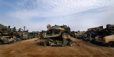 U.S. military vehicles rendered useless by improvised explosive devices litter a military scrap yard at Camp Al Asad in Iraq's anbar province.