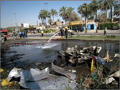 Iraqi firefighters clean up the site where a parked car bomb killed 10 and wounded 25 people in the Karradah neighborhood in downtown Baghdad on Sunday.