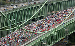 Thousands of people walk on the road deck during the grand opening of the new Tacoma Narrows Bridge Sunday in Tacoma, Wash.