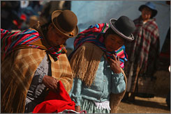 Two Aymara women wearing traditional clothes shop for used clothing at a street market in El Alto, Bolivia. More than $1.2 billion in stained T-shirts, stretched-neck sweaters and other clothing cleared out of wealthy nations' closets end up in the developing world each year.