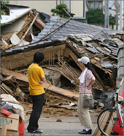 Residents of Kashiwazaki city look at their collapsed house on Tuesday. 13,000 quake victims have crowded into emergency shelters a day after the quake.