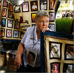 Victoria Martin, an alleged victim of abuse by a priest, holds a quilt with faces of other victims at the Los Angeles County Courthouse on Monday where the record settlement was approved.
