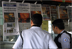 Policemen read Brazil's morning newspapers with the front pages showing the crash at Congonhas Airport.