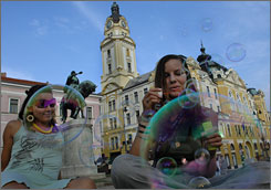 Hungarian girls blow soap bubbles as they rest in the main square of Pecs. The city has over 2,000 years of its history on display, including Roman ruins and remnants of Muslim structures left behind by the Turks.