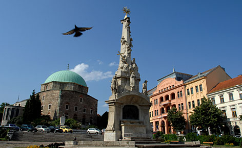 A pigeon flies over the Holy Trinity Column and the Parish Church, a former mosque of Pasha Gazi Kassim built by the Turks, in the main square of Pecs, Hungary, a city 125 miles south of Budapest that will be named a 'European Capital of Culture' in 2010.