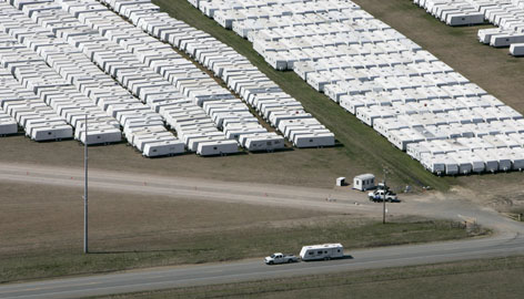 A pickup tows one of about 20,000 mobile homes and travel trailers owned by the Federal Emergency Management Agency from Hope Municipal Airport near Hope, Ark., in this March 2007, file photo.