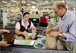 Rep. Dave Loebsack, D-Iowa, helps cashier Jasmine Stanford, 18, by bagging groceries at Tom's Market and Meats in Burlington, Iowa. Loebsack was at the supermarket to highlight an increase in the federal minimum wage which goes up Tuesday.