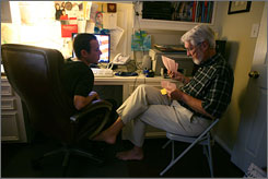 Assistant/nurse Christian Brown assists Richard Taylor, who has early-stage Alzheimer's, with paying bills in his home office in Houston.