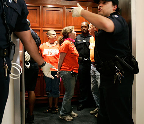 Capitol Police arrest anti-war activists who gather in the office of Rep. John Conyers as they participate in a civil disobedience after Conyers' meeting with activist Cindy Sheehan on Capitol Hill on Monday.