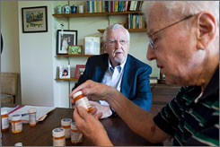 "Retired physician Jonathan Fine, left, helps Sumner Kaplan, 88, sort his medications at Kaplan's Boston home. Fine, 75, started Bedside Advocates in 2005, and recruits volunteers to guide patients through their care and ""translate"" medical information."