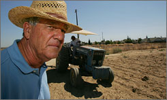 Third-generation farmer Bill Chandler stands in his empty field which butts up against housing development in Parlier, Calif. Farmers like Chandler are finding it increasingly difficult to turn down lucrative offers to turn their farmland into housing development.