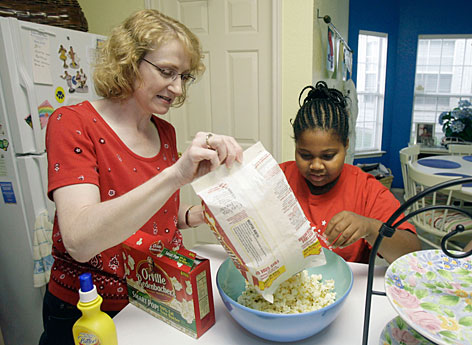 Sue Washington, left, works with her daughter Alana Washington, 9, to make a popcorn snack on Wednesday, June 13, 2007, in Dallas. It's been more than two months since the Washington family completed a program for children struggling with their weight and now they're trying to stick to their nutrition and fitness goals.