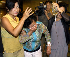 Family members hold up Sung-Min's mother after she learns that he was killed by the Taliban.