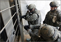 U.S. soldiers break a chain to search a house in the Amariyah neighborhood in Baghdad on Tuesday.