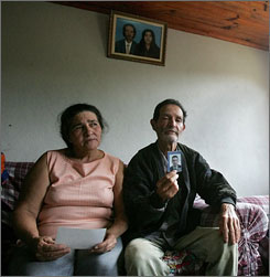 Maria Otone de Menezes, left, and her husband Matuzinho, right, mother and father of Jean Charles de Menezes, hold up a picture of him at their home near Gonzaga, Brazil, in 2005. Menezes, 27, was killed in London two years ago, in a subway station.