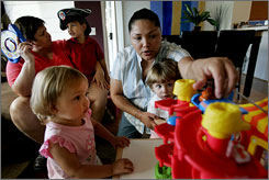 Guadalupe Benitez, right, plays with twin daughters Sophia, left, and Shane, 2, as her partner Joanne Clark holds son Gabriel, 5, at their home in Oceanside, Calif. Benitez has sued two doctors for refusing to artificially inseminate her for religious reasons.