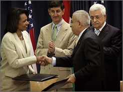 Rice and Palestinian Prime Minister Salam Fayyad shake hands after signing an agreement, granting the Palestinians $80 million for reform of their security services.