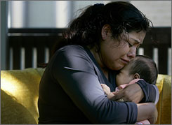 Abundia Martinez, 31, weeps as she hugs her 2-month-old daughter, Lorena Trinidad Martinez, at their home after speaking to her family in Mexico to give news of her husband, Artemio Trinidad-Mena, 29, who was killed in Wednesday's bridge collapse. He is also survived by three young children in Mexico.