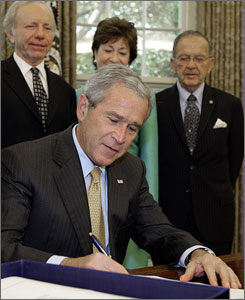 President Bush signs the 9/11 Commission Act of 2007 in the Oval Office at the White House in Washington, D.C., Friday. Standing behind the president, from left to right, are Sen. Joseph Lieberman, Sen. Susan Collins, and Sen. Ted Stevens.