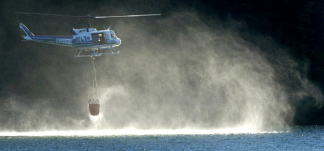 A helicopter dips its bucket into Lake Easton to help put out a wildfire that started when a helicopter crashed Thursday, near Easton, Wash. All four were believed to have died, Kittitas County Undersheriff Clayton Myers said, but authorities could not confirm their fate because the fire was preventing them from reaching the helicopter.