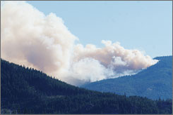 Smoke rises from a forest fire sparked by the helicopter crash Thursday, near Easton, Wash. By 7:30 p.m, the fire had grown to about 300 acres, according to Mark Grassel, a state Department of Natural Resources fire spokesman.