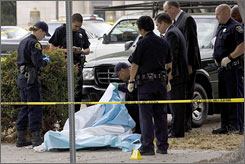 Oakland police officers investigate the scene where Oakland Post editor Chauncey Bailey was shot to death   in Oakland, Thursday. Bailey's murder might be tied to police raids on a well-known Oakland bakery that rounded up 19 people, as well as a small armory of weapons on Friday.