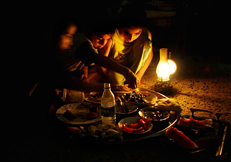 The Abu Mustafa family eats dinner by the light of an oil lamp in the Shiite neighborhood of Sadr City in Baghdad. The family lives on a block that gets only one or two hours of electricity per day.
