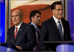 Republican Presidental hopefuls former New York City Mayor Rudy Giuliani, left, and former Massachusetts Governor Mitt Romney, right, conclude their debate by speaking with supporters. Romney leads the other Republican candidates in Iowa.