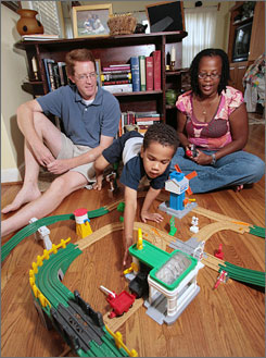 Whitney and Roslyn Holcomb entertain their 3-year-old son, Luke, with his train set at their home. Census data showed 117,000 black wife-white husband couples in 2006, up from 95,000 in 2000.