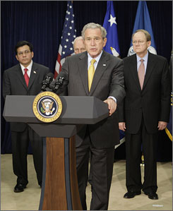 Some Democrats complained that a bill the president signed into law Sunday gives too much authority to National Director of Intelligence Mike McConnell, behind Bush right, and Attorney General Alberto Gonzales, behind Bush left, without enough judicial oversight.