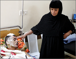 Umm Jihad, right, watches over her son, Jihad Wali, 35, a victim of a roadside bomb that killed nine civilians and wounded eight, in a central Baghdad on Monday.